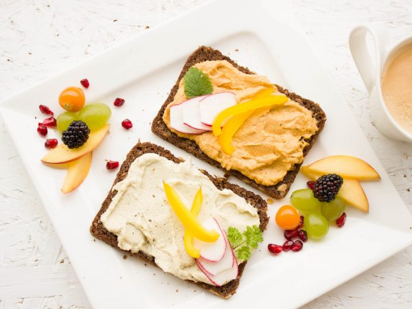 Two slices of whole grain toast spread with hummus and a side of fresh fruit on a white plate