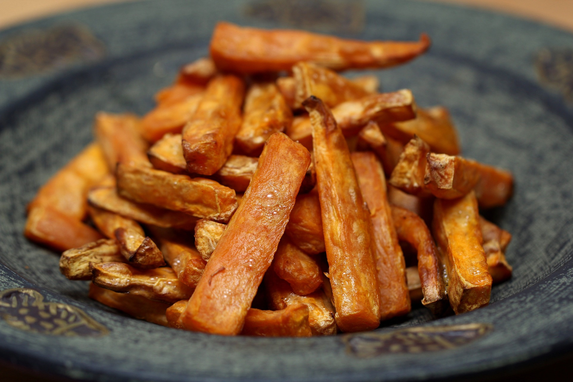 Sticks of roasted sweet potatoes piled on a gray bowl