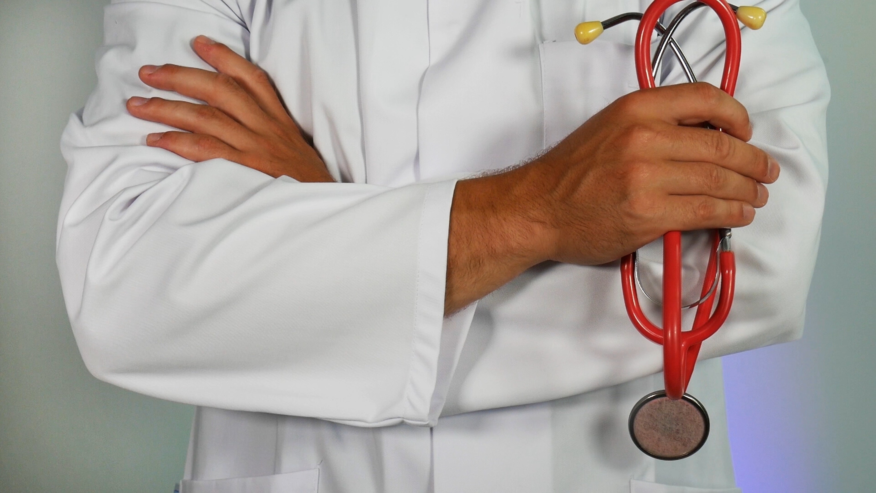 Midsection of a doctor wearing a white lab coat holding a red stethoscope with arms crossed