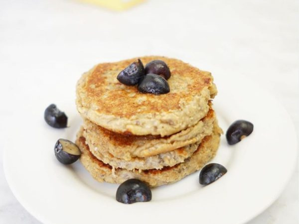 Stack of pancakes made with iron-fortified baby cereal on a white plate topped with blueberries