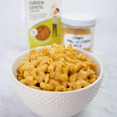 White bowl of vegan mac and cheese next to ingredients