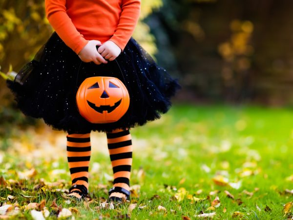 Little girl holding pumpkin bucket for trick or treating