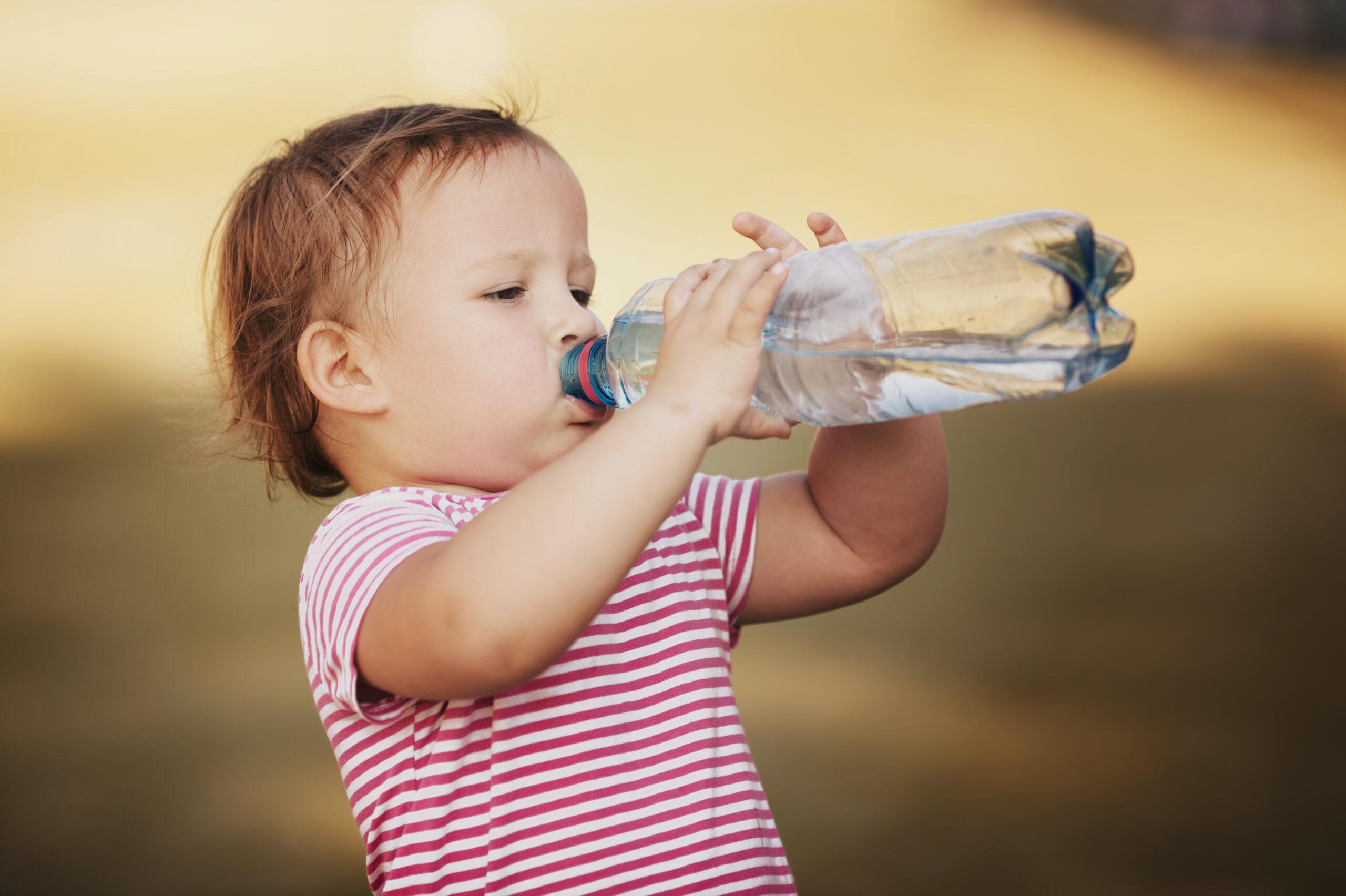 little girl drinking water from a plastic bottle